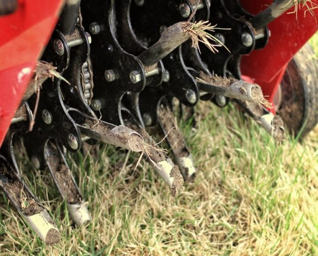 Close up of a mechanical lawn aerator.